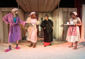 Stepfamily (from left to right) Zonita (Drew Watkins), Shaniqua (Ladidi Garba), and Evil Stepmother (Clara McDaniels) mistreats Cinderella (Regina V. Fields) in African-American Shakespeare Company's 2014 production of Cinderella.