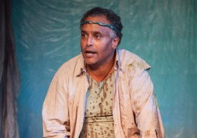 Prospero (Michael Gene Sullivan) on an island made of debris. African-American Shakespeare Company's The Tempest Photo Credit: Lance Huntley
