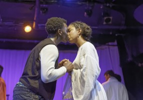Romeo (Wilgens Pierre) and Juliet (Jazara Metcalf) share their first kiss in African-American Shakespeare Company's Romeo and Juliet. Photo Credit: Lance Huntley